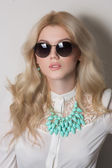Blonde with long hair in necklace. sunglasses — Stock Photo