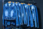 Fashion jeans jacket on hangers — Stock Photo