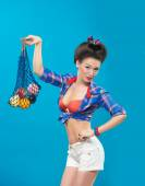 Woman with pin-up make-up with a bag of fruit — Stock Photo