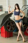Girl mechanic replace tires on wheels — Stock Photo
