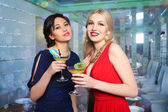Girls clinking glasses of cocktails at the party — Stock Photo