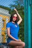 Young woman posing outdoor over fence mesh — Stock Photo