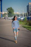 Belle fille brune se promène dans les rues de la ville. en redingote et jeans déchirés — Photo