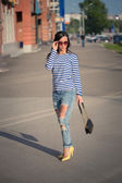 Beautiful brunette girl walks through the city streets. in torn jeans and frock — Stock Photo