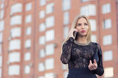 Business woman speaking cellphone on the street — Stock Photo