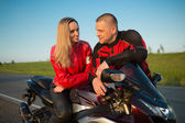 Biker man and woman sitting on a motorcycle. — Stock fotografie