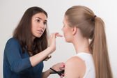 Make-up artist doing make-up of a beautiful young girl — Stock Photo
