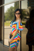 Girl in colorful dress and sunglasses on the street — Stock Photo