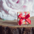 Gift box with red bow on wood background — Stock Photo #77528082