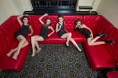 Four girl in black short dress on a red couch — Stock Photo