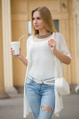 Stylish woman drinking coffee to go in a city street — Stock Photo