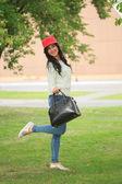 Девочка в Красная шапка с ушками, держит мешок на улице — Стоковое фото