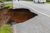 Collapse of the road. Condition of the road to water erosion as  — Stock Photo