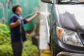 Blur of man using pressure washer for washing a car — Photo