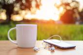 Coffee cup and smartphone on the table in sunset time — Foto Stock