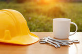 Close up coffee cup and safety helmet on the table — ストック写真