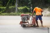 Cutting asphalt road for repair by hydraulic driven angle grinde — Stock Photo