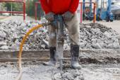 Worker using construction drilling cement on the ground — Zdjęcie stockowe