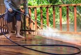 Thai man do a pressure washing on timber — Stock Photo