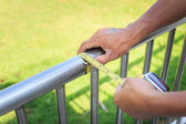 Man measuring stainless steel railing with measuring tape. — Stock Photo