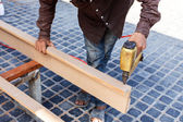 Hand holding nail gun to fix the wood — Stock Photo