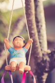 Clay doll on swing — Stock Photo