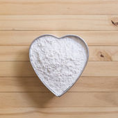 Flour in heart-shape pan — Stock Photo