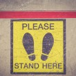 PLEASE STAND HERE foot sign — Stock Photo #66584857