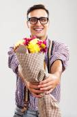 Nerdy man is giving a bouquet of flowers — Stock Photo