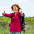 Woman with backpack is ready for hiking and she is showing thumbs up — Stock Photo #60033633