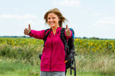 Woman with backpack is ready for hiking and she is showing thumbs up — Stock Photo