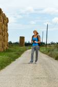 Woman with backpack and binoculars enjoys walking the country road — Stock Photo