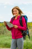 Woman with backpack is holding a map — Stock Photo