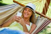 Woman is lying on hammock and using mobile phone — Stock Photo