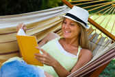 Woman is lying on hammock with book — 图库照片