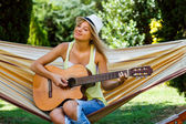 Woman is sitting on hammock and playing her guitar — Stock Photo