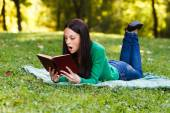 Woman suprised reading a book outdoors — Stock Photo