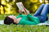 Woman reading a book outdoors — Stock Photo