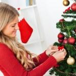 Blond woman decorating Christmas tree — Stock Photo #60195671