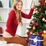 Blond woman decorating Christmas tree — Stock Photo #60195687