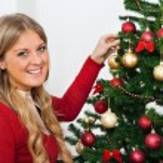 Blond woman decorating Christmas tree — Stock Photo #60195689