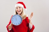 Beautiful woman is excited, holding clock — Stock Photo