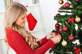 Blond woman decorating Christmas tree — Stock Photo