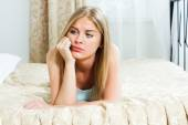 Blond sad woman in bed — Stock Photo