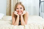 Blonde woman lying on her bed — Stock Photo