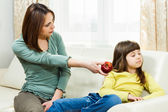Mother is giving apple to her angry daughter — Stockfoto