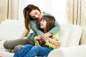 Mother and daughter sitting on sofa at their home — Foto Stock