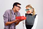 Nerdy man is giving a present to his nerdy lady — Stock Photo