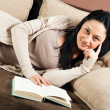 Woman lying on the sofa and reading a book — Foto Stock #60724777