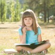 Little schoolgirl doing her homework in the park — Photo #60724983
